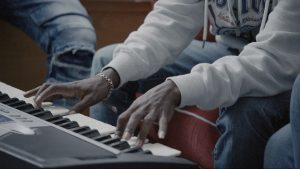 Meron on his keyboard. Still from the Film Academy documentaire 'The Boys Next Door'.